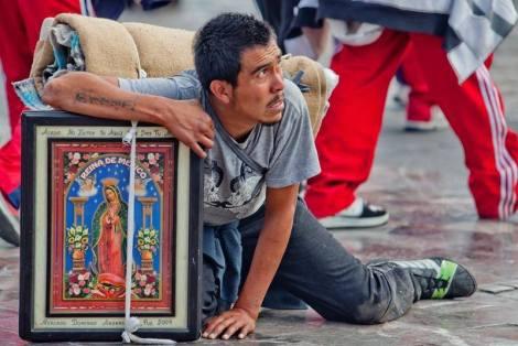 Peregrino postrado exhausto en el suelo. Basílica de Nuestra Señora de Guadalupe, Ciudad de México, México.